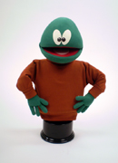 Green puppet with unusual eyes and bald head.