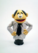 Yellow man puppet with salt and pepper balding hair and long sleeve shirt and tie.