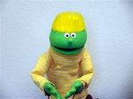 small green puppet with yellow flat top hair