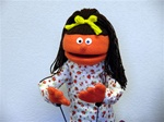 Tiny hand puppet girl with orange skin and brown ponytail.