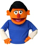 Skip is an orange puppet puppet with black hair.