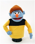 Herb is a blue boy puppet with auburn hair.