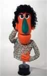 "This 24"" inch tall woman puppet is orange with black curly hair."